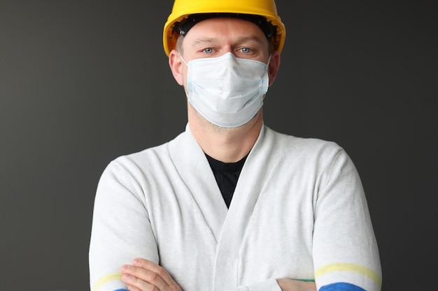 Mannelijke bouwvakker in gele kaste en medisch beschermend masker coronavirus pandemie
