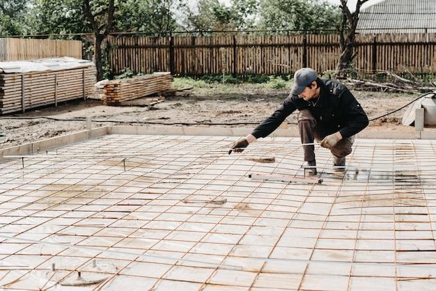 Mannelijke bouwvakker installeert metalen hulpstukken voor de fundering van de constructie van een huis onder het gieten van beton