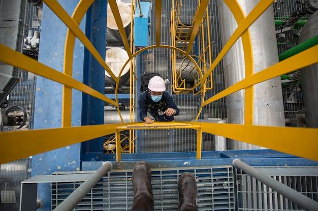 Mannelijke bovenaanzicht beklim de trap steigers inspectie pijpleiding elektriciteitstransmissie onderstation en elektriciteitscentrale