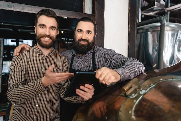 Mannelijke brouwers met productiecontrole voor tabletbieren.