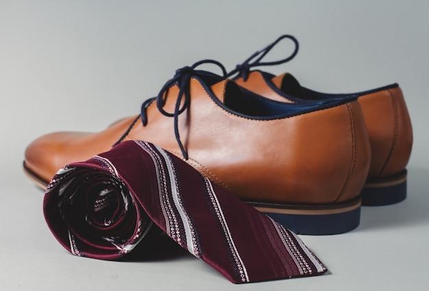 Mannelijke bruine schoenen met stropdas op grijze tafel