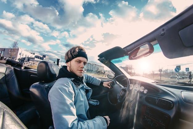 Mannelijke chauffeur rijdt in een cabrio door de stad