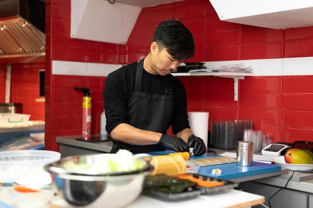 Mannelijke chef-kok bereidt een sushi-bestelling voor een afhaalmaaltijd