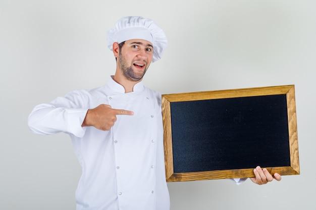Mannelijke chef-kok die bord met vinger in wit uniform toont en positief kijkt