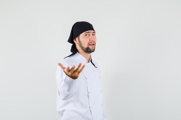 Mannelijke chef-kok die de hand op een vragende manier in wit uniform uitrekt en er zelfverzekerd uitziet. vooraanzicht.
