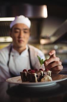 Mannelijke chef-kok die dessertbord versieren