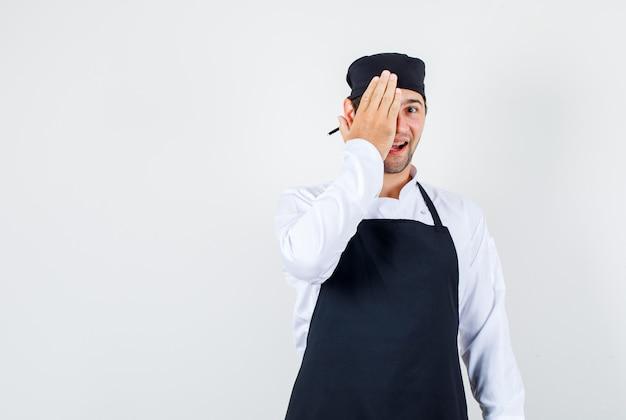 Mannelijke chef-kok die één oog bedekt met dient uniform, schort in en kijkt vrolijk, vooraanzicht.