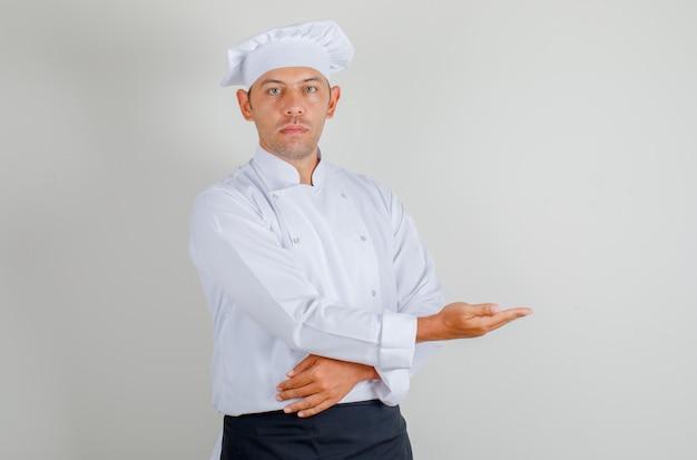 Mannelijke chef-kok die gasten in uniform, schort en hoed uitnodigt en uitnodigt en zelfverzekerd kijkt