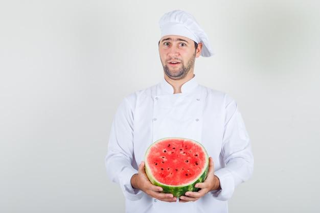 Mannelijke chef-kok die gesneden watermeloen in wit uniform houdt en positief kijkt.