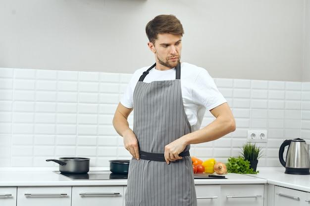 Mannelijke chef-kok die in schorten het gezonde voedselrecept van de voedselkeuken koken