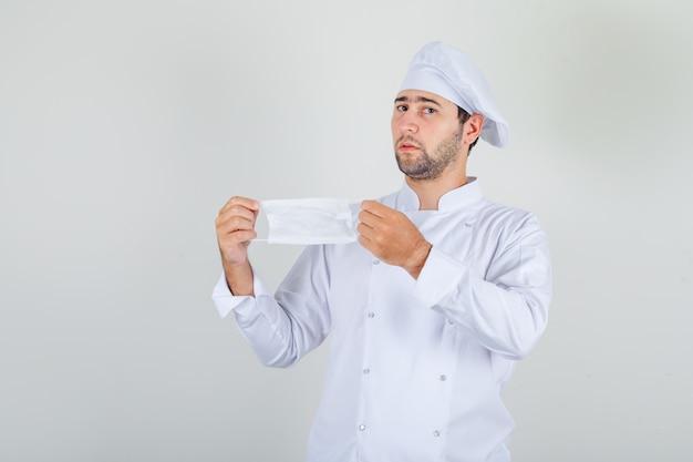 Mannelijke chef-kok die medisch masker in wit uniform houdt en aarzelend kijkt.