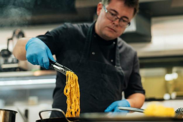 Mannelijke chef-kok die met handschoenen deegwaren maakt