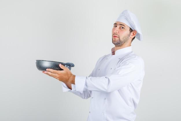 Mannelijke chef-kok die pan in wit uniform houdt en trots kijkt