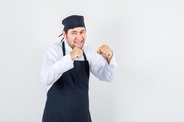 Mannelijke chef-kok die tanden in bokser balde stelt in uniform, schort en ziet er vrolijk uit. vooraanzicht.