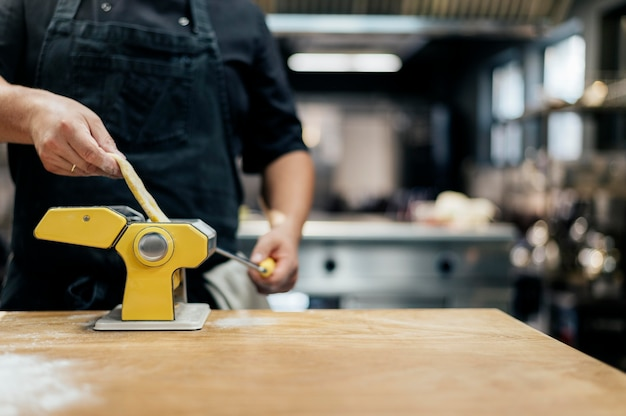 Mannelijke chef-kok die vers pastadeeg rolt