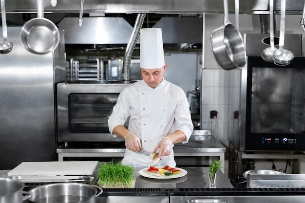 Mannelijke chef-kok die voedsel in de keuken versieren