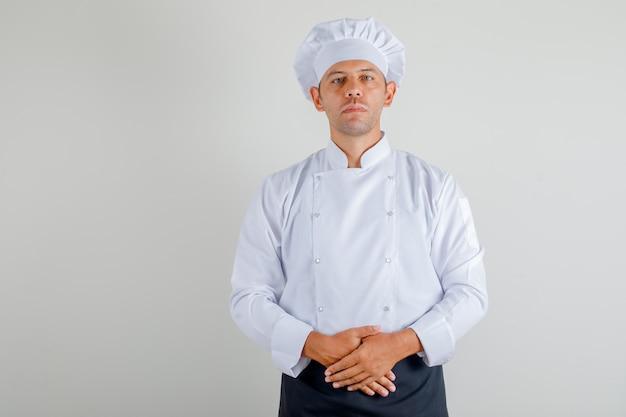 Mannelijke chef-kok die zich klaar om in uniform, schort en hoed te koken bevindt