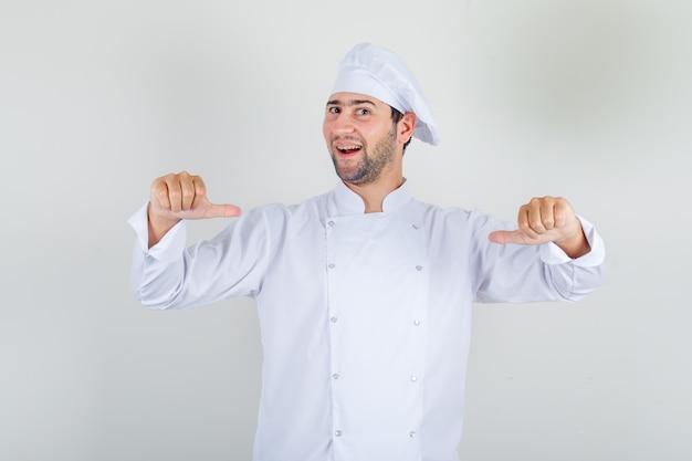 Mannelijke chef-kok die zich met duimen in wit uniform toont en trots kijkt.