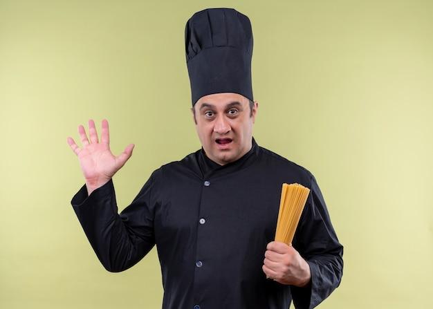 Mannelijke chef-kok die zwart uniform draagt en de spaghetti van de de holdingsrij van de kokhoed kijkt verbaasd en verbaasd met opgeheven hand die zich over groene achtergrond bevindt