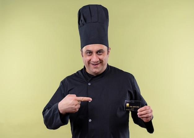 Mannelijke chef-kok die zwarte uniform draagt en de creditcard van de kokhoedholding met vinger aan het richt die vrolijk glimlacht zich over groene achtergrond bevindt