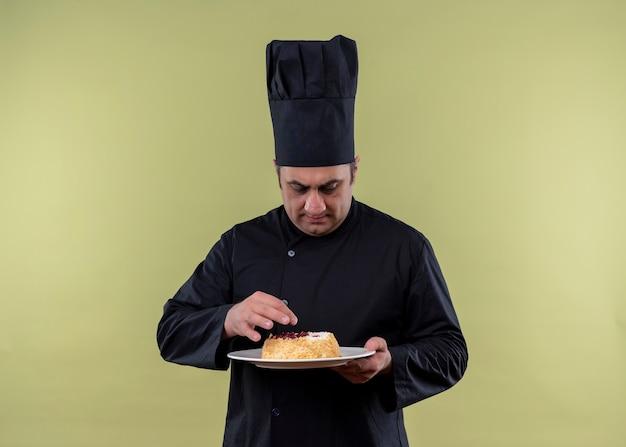 Mannelijke chef-kok die zwarte uniform draagt en de plaat van de kokhoedholding met cake bekijkt die het met ernstig gezicht bekijkt dat zich over groene achtergrond bevindt