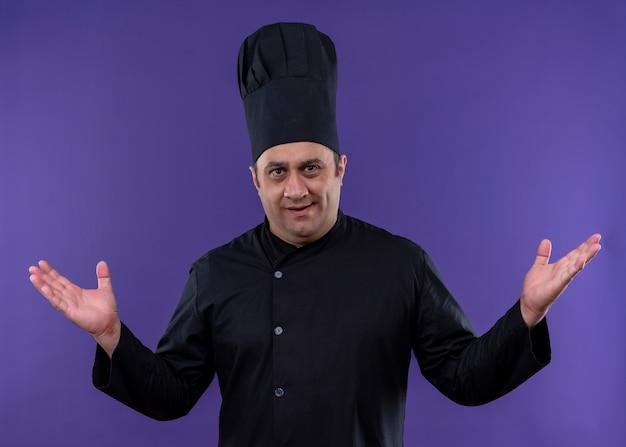 Mannelijke chef-kok die zwarte uniform draagt en kokhoed bekijkt die camera bekijkt ontevreden het opheffen van wapens die zich over purpere achtergrond bevinden