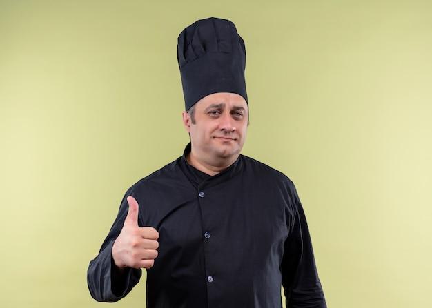 Mannelijke chef-kok die zwarte uniform draagt en kokhoed bekijkt die camera met glimlach op gezicht bekijkt die duimen toont die zich over groene achtergrond bevinden