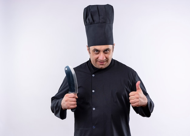Mannelijke chef-kok die zwarte uniform draagt en kokhoed die scherp keukenmes houdt die het tonen duimen omhoog toont die zich over witte achtergrond bevinden