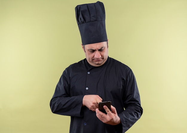 Mannelijke chef-kok die zwarte uniform draagt en kokhoed houdt smartphone sms'en naar iemand met een ernstig gezicht dat zich over groene achtergrond bevindt