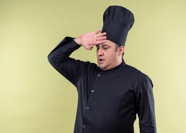 Mannelijke chef-kok die zwarte uniform draagt en kokhoed kijkt die moe en overwerkt met hand boven hoofd zich over groene achtergrond bevindt