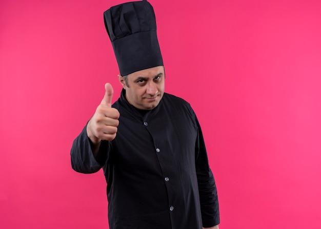 Mannelijke chef-kok die zwarte uniform draagt en kookhoed bekijkt camera het glimlachen toont duimen die zich over roze achtergrond bevinden