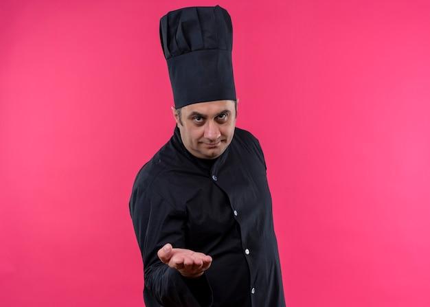 Mannelijke chef-kok die zwarte uniform draagt en kookhoed bekijkt die camera bekijkt die hand greenting aanbiedt die zich over roze achtergrond bevindt