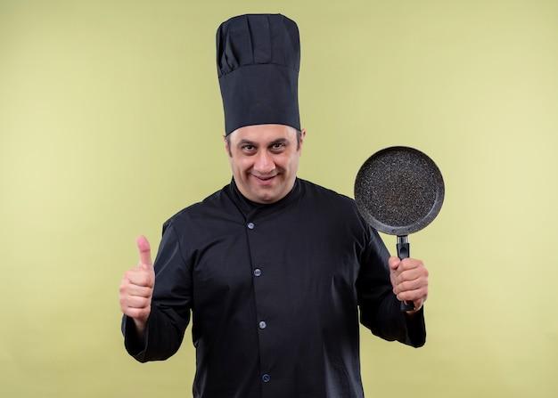 Mannelijke chef-kok die zwarte uniform draagt en kookhoed die een pan houdt die duimen toont die zich omhoog glimlachen bevinden over groene achtergrond