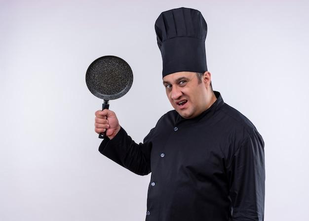 Mannelijke chef-kok die zwarte uniform draagt en kookhoed die een pan met boos gezicht slingert die zich over witte achtergrond bevinden