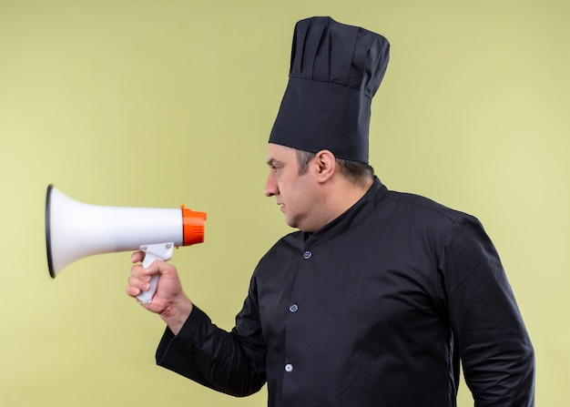 Mannelijke chef-kok die zwarte uniform draagt en kookhoed die opzij met de ernstige megafoon van de gezichtsholding kijkt die zich over groene achtergrond bevindt