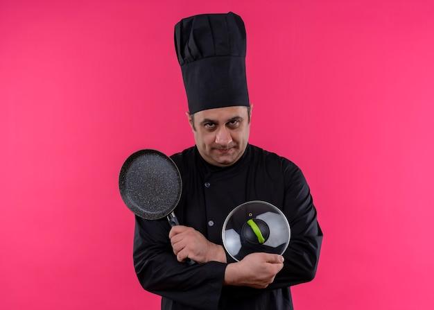 Mannelijke chef-kok die zwarte uniform draagt en kookhoed houdt steelpan die handen kruist die camera met ernstig gezicht bekijkt dat zich over roze achtergrond bevindt