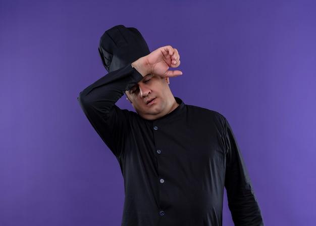 Mannelijke chef-kok die zwarte uniform draagt en kookhoed kijkt moe en overwerkt met hand boven hoofd die zich over purpere achtergrond bevindt
