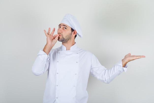 Mannelijke chef-kok doet heerlijk gebaar in wit uniform