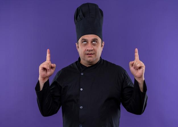 Mannelijke chef-kok dragen zwart uniform en kok hoed opzoeken wijzend met wijsvingers staande over paarse achtergrond