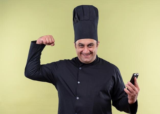 Mannelijke chef-kok dragen zwarte uniform en kok hoed bedrijf smartphone balde vuist op zoek opgewonden en gelukkig staande over groene achtergrond