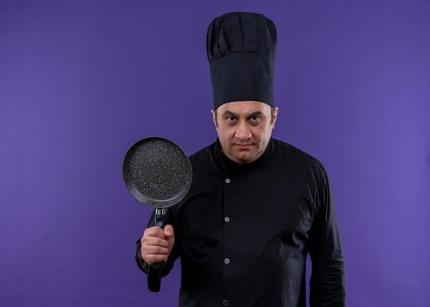 Mannelijke chef-kok dragen zwarte uniform en koken hoed bedrijf koekenpan camera kijken met ernstige uitdrukking op gezicht staande over paarse achtergrond