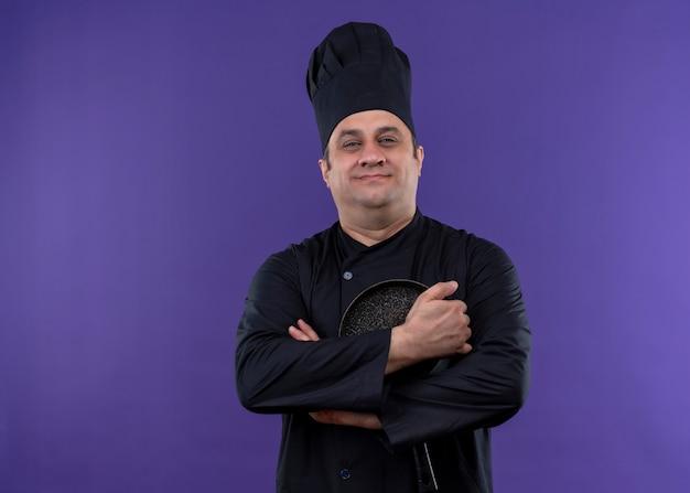 Mannelijke chef-kok dragen zwarte uniform en koken hoed houden koekenpan camera kijken met zelfverzekerde glimlach staande over paarse achtergrond