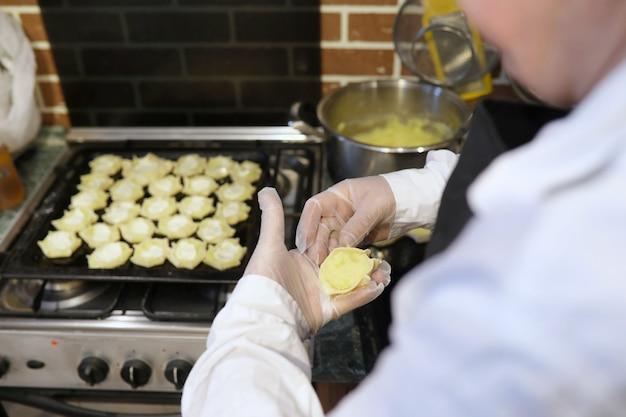 Mannelijke chef-kok gebruikt ingrediënten voor het bereiden van meelproducten op de keukentafel