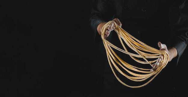 Mannelijke chef-kok handen maken van verse zelfgemaakte noedels op blaack achtergrond