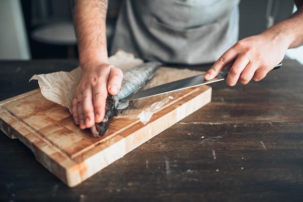 Mannelijke chef-kok handen met mes gesneden rauwe vis op snijplank