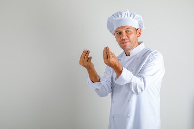 Mannelijke chef-kok in hoed en uniform doen italiaans gebaar met vingers