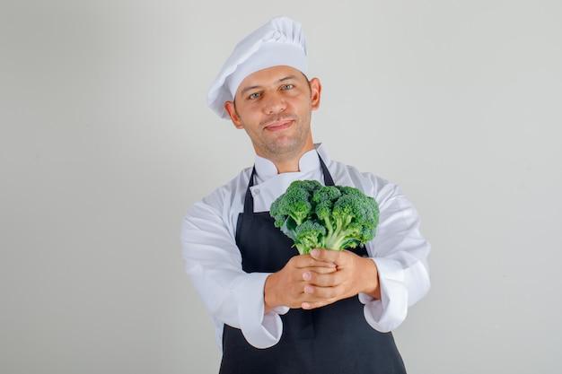 Mannelijke chef-kok in hoed, schort en eenvormige holdingsbroccoli en het glimlachen