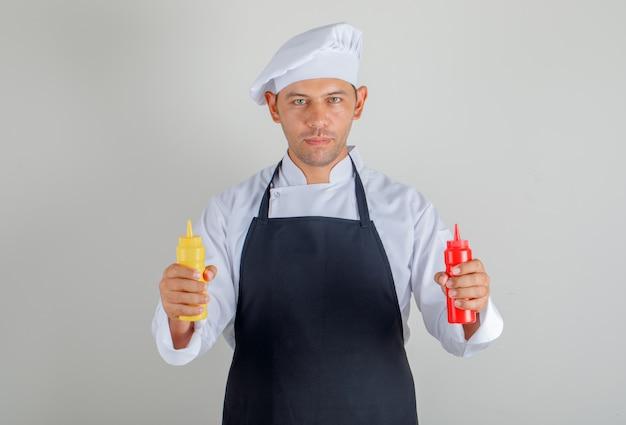 Mannelijke chef-kok in hoed, schort en uniforme holding flessen ketchup en mosterd