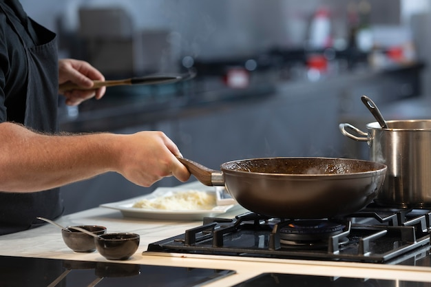 Mannelijke chef-kok in keuken close-up koken