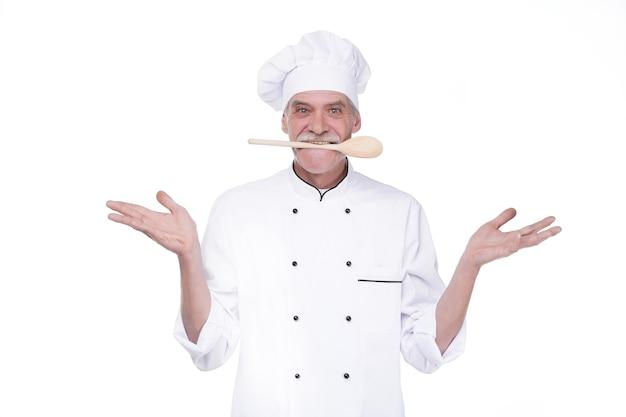 Mannelijke chef-kok in uniform die een houten lepel op de muis houdt terwijl hij op de witte muur blijft?